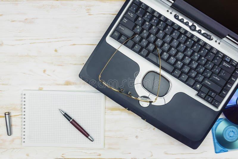 Alter Laptop mit Laserscheibe, Taschenrechner, Notizbuch, Gläser und lizenzfreie stockfotos