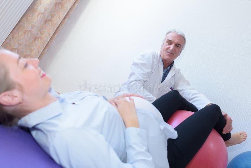 Alter männlicher Doktor mit der schwangeren Frau, die auf Eignungsball sitzt lizenzfreies stockbild