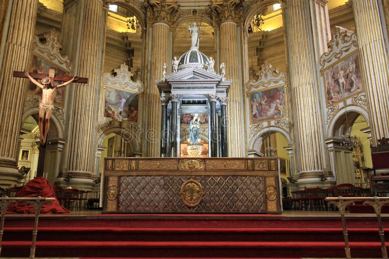 The alter in Malaga Cathedral. With a crucifix and red carpet stock photos