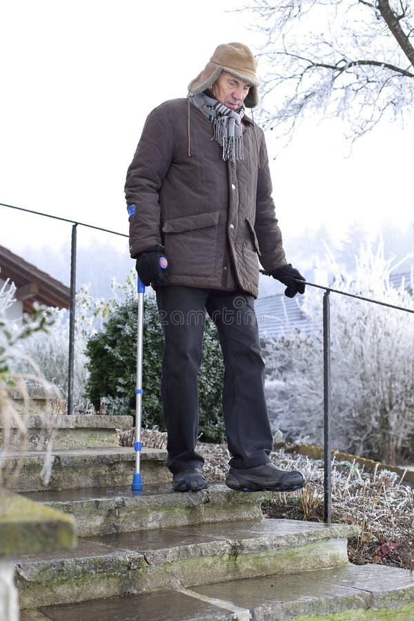 Alter Mann auf Krücken auf eisiger Treppe im Winter stockfotografie
