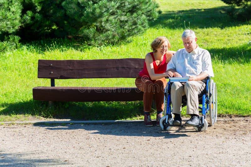 Alter Mann auf Rollstuhl und junger Frau auf einer Bank stockbild