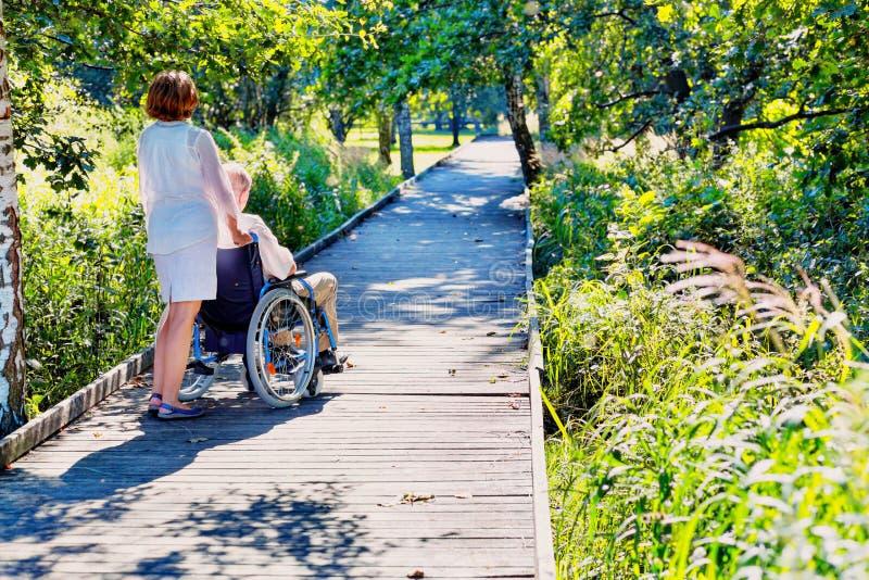 Alter Mann auf Rollstuhl und junger Frau im Park stockbild