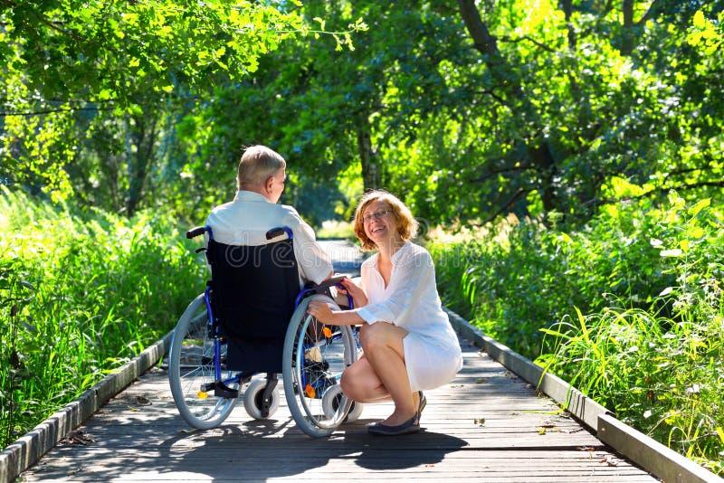 Alter Mann auf Rollstuhl und junger Frau im Park stockfotos
