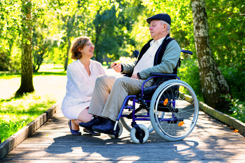 Alter Mann auf Rollstuhl und junger Frau im Park stockbilder