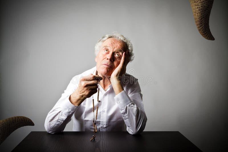 Alter Mann betet mit Rosenkranzperlen Gebet und Versuchung lizenzfreie stockbilder
