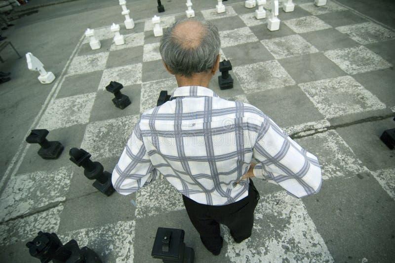 Alter Mann, der Überformatschach-Vorstand spielt stockbild