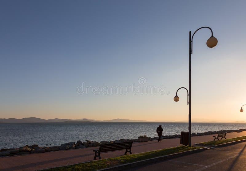 Alter Mann, der allein nahe einem See bei Sonnenuntergang geht stockbilder