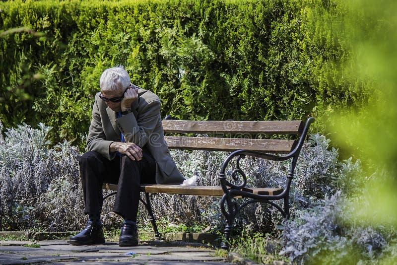 Alter Mann, der auf einer Bank im Seepark von Burgas/von Bulgarien/04 sitzt 18 2015/ stockbilder