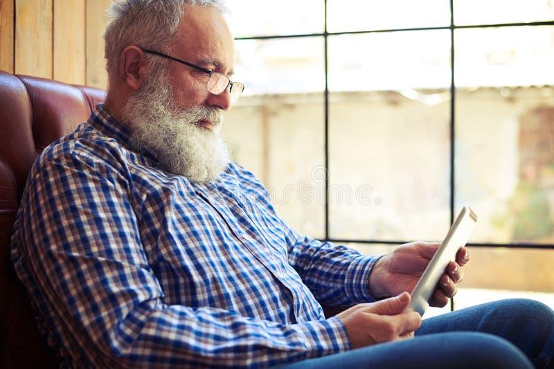 Alter Mann, der auf Sofa stillsteht und Tabletten-PC verwendet lizenzfreies stockfoto