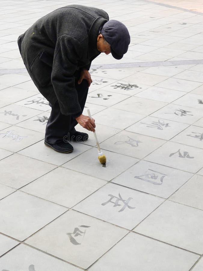 Alter Mann, der chinesische Handschrift auf den Fußboden schreibt lizenzfreies stockfoto