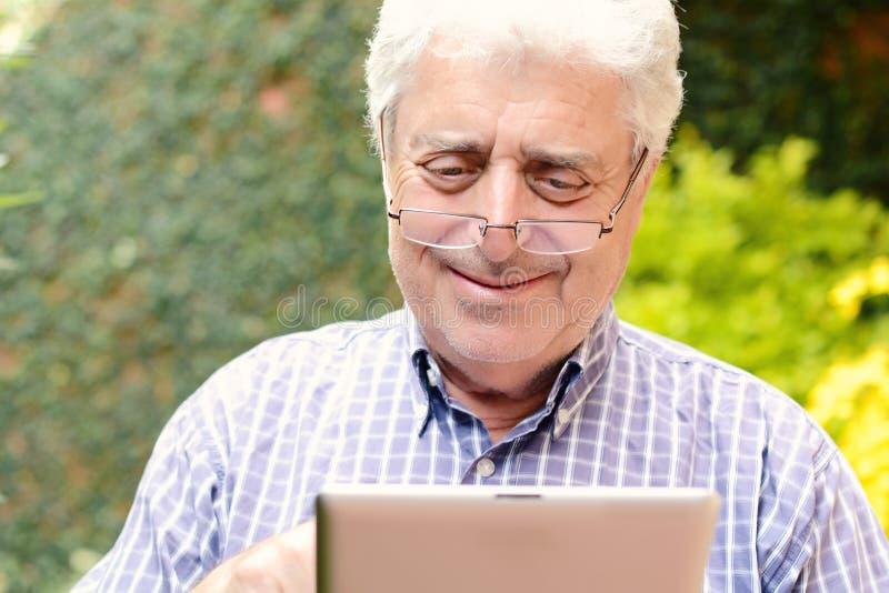 Alter Mann, der digitale Tablette verwendet stockfoto