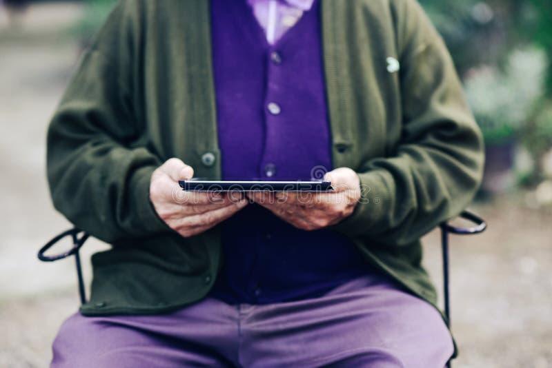 Alter Mann, der draußen einen Tablet-Computer verwendet stockfotografie