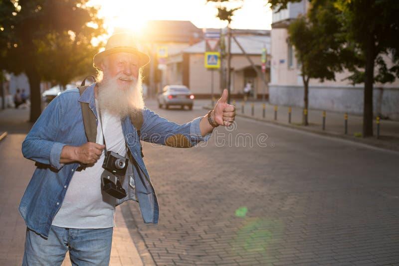 Alter Mann, der durch das Per Anhalter fahren reist lizenzfreie stockfotografie