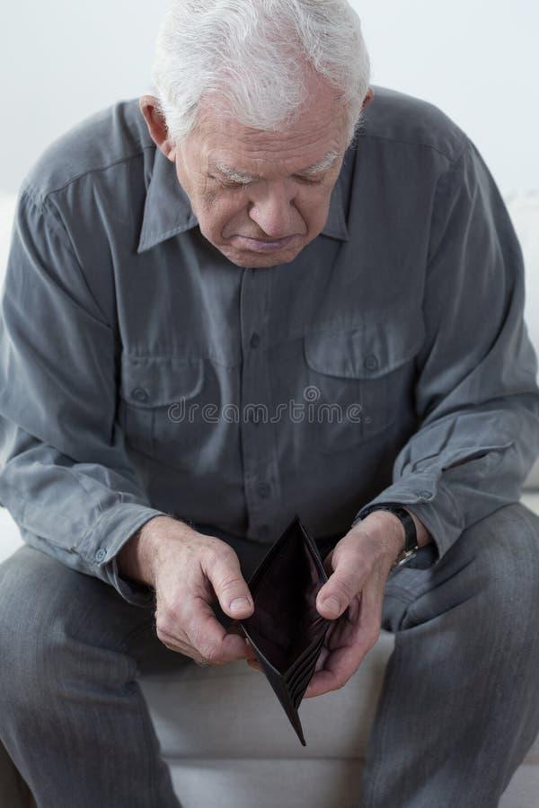 Alter Mann, der eine leere Geldbörse betrachtet lizenzfreies stockbild