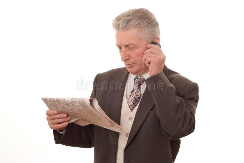 Alter Mann, der eine Zeitung auf Weiß liest stockfoto