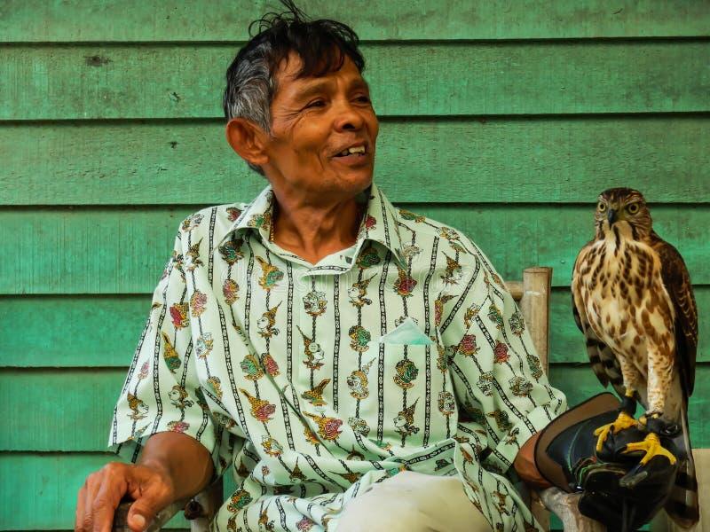 Alter Mann, der einen Falken auf seinem Arm an sich hin- und herbewegendem Kennzeichen Sam Pan Nams hält stockfotos