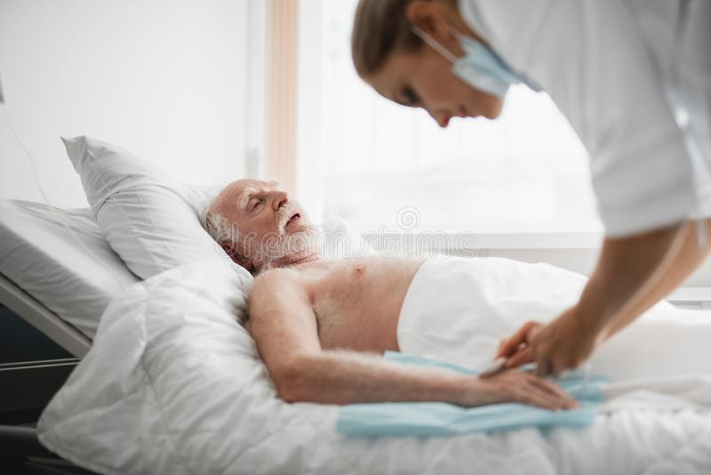 Alter Mann, der im Krankenhausbett während des medizinischen Verfahrens liegt lizenzfreies stockfoto