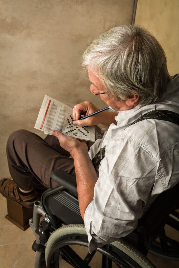 Alter Mann, der Kreuzworträtsel löst lizenzfreies stockfoto
