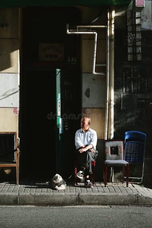 Alter Mann, der mit einem Hund vor seinem Haus sitzt lizenzfreie stockfotos