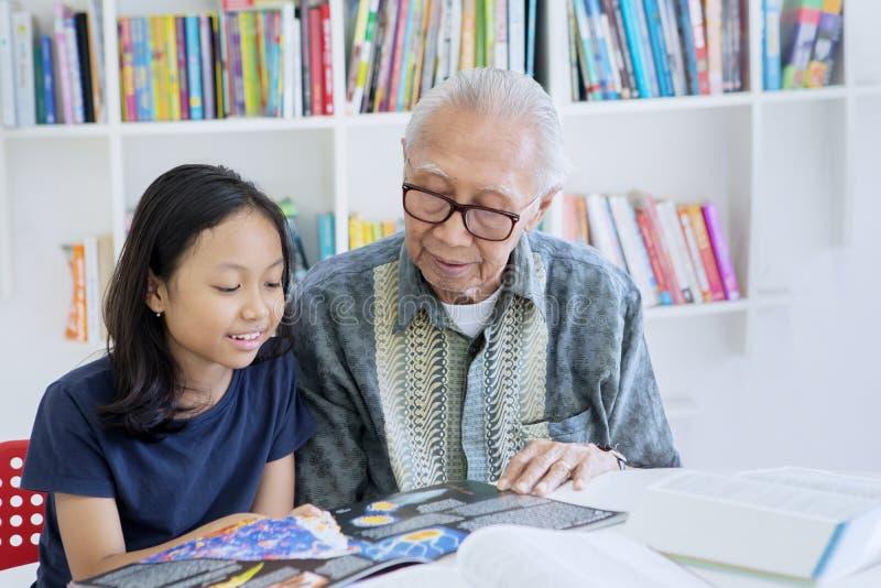 Alter Mann, der seine Enkelin unterrichtet, ein Buch zu lesen stockfotos