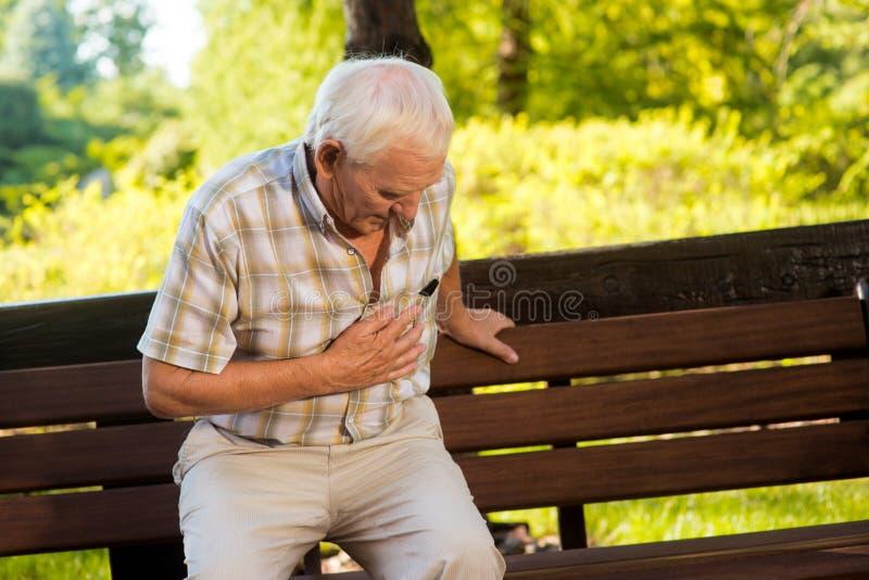 Alter Mann, der seinen Magen hält stockfotografie