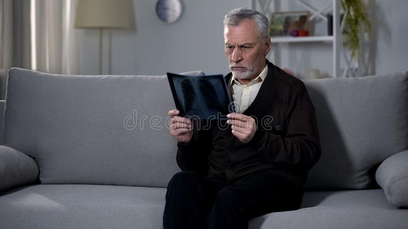 Alter Mann, der traurig Röntgenstrahlbild, Schwierigkeit fertig wird mit Terminaldiagnose betrachtet lizenzfreie stockfotos
