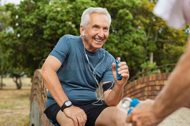 Alter Mann, der unter Verwendung des Handgreifers trainiert lizenzfreie stockfotos