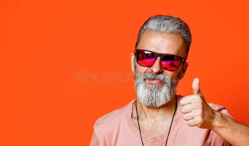 Alter Mann des Bartes zeigt sich Daumen stockbilder