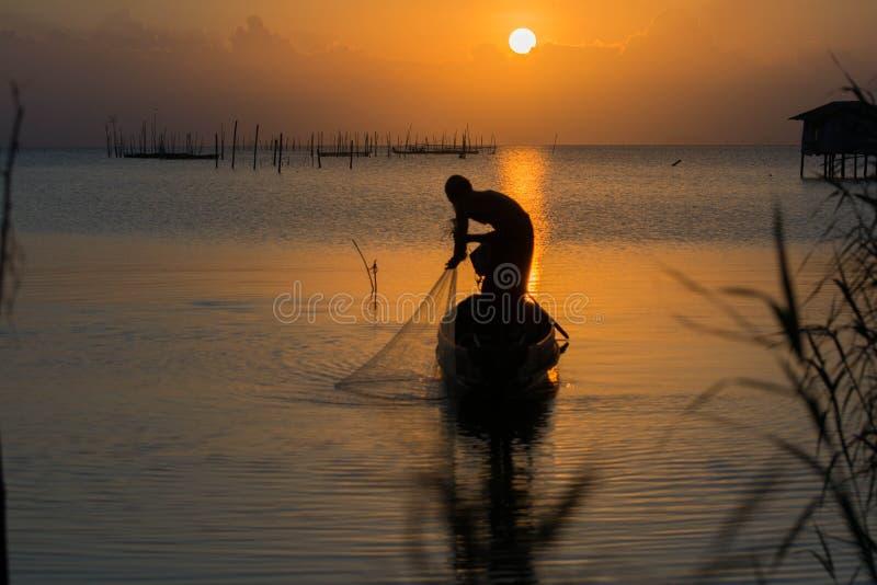 Alter Mann fischen bei Sonnenuntergang von Thailand lizenzfreie stockfotos