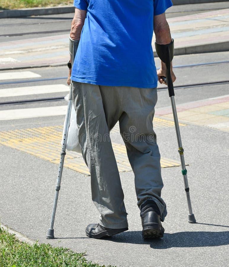 Alter Mann geht mit Krücken lizenzfreie stockfotos
