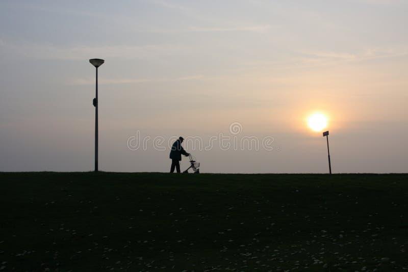 Alter Mann geht mit seinem rollator bei Sonnenuntergang stockfotos