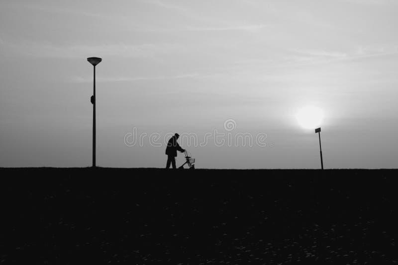 Alter Mann geht mit seinem rollator bei Sonnenuntergang stockfoto