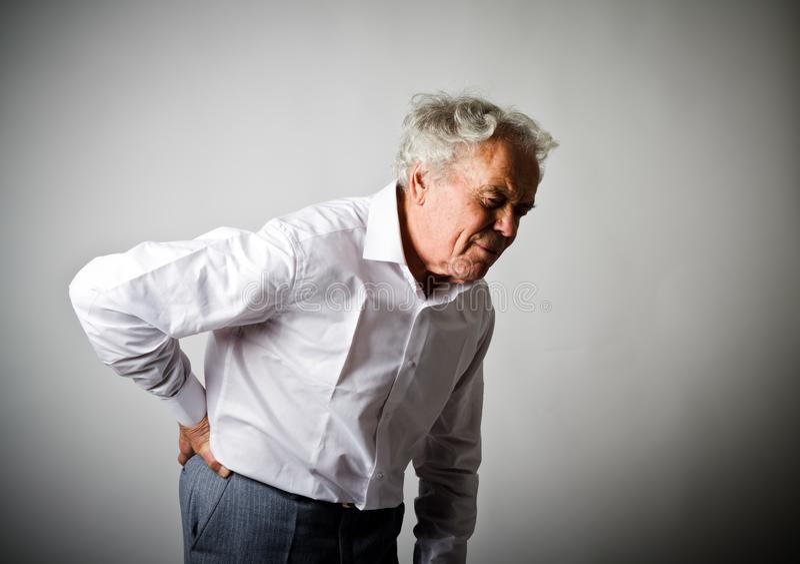 Alter Mann hat Rückenschmerzen stockfotografie