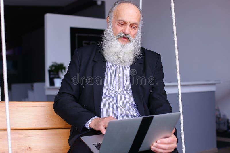 Alter Mann im Ruhestand benutzt Laptop und verständigt sich mit Kollegen beh lizenzfreie stockfotos