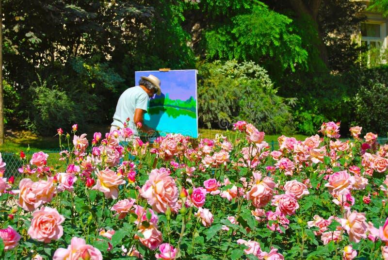 Alter Mann-Künstler Painting Outdoors in Rose Garden lizenzfreie stockfotos