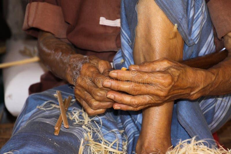 Alter Mann mit den braunen dünnen Händen, die mit Bambusholz in einer Papierregenschirmfabrik in Chiang Mai arbeiten stockfoto