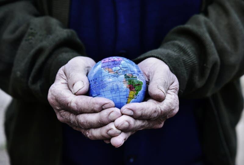 Alter Mann mit einer Weltkugel in seinen Händen lizenzfreie stockfotografie