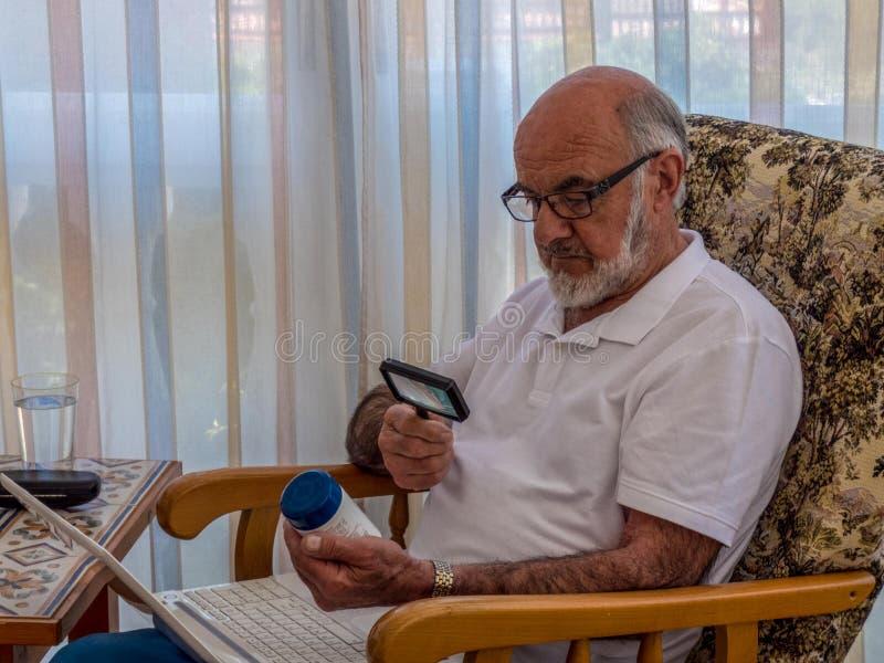 Alter Mann mit Lupenlesung auf dem Glas mit Vitaminen lizenzfreie stockfotografie