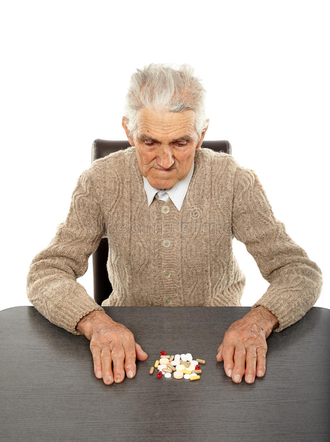 Alter Mann mit Pillen stockbild