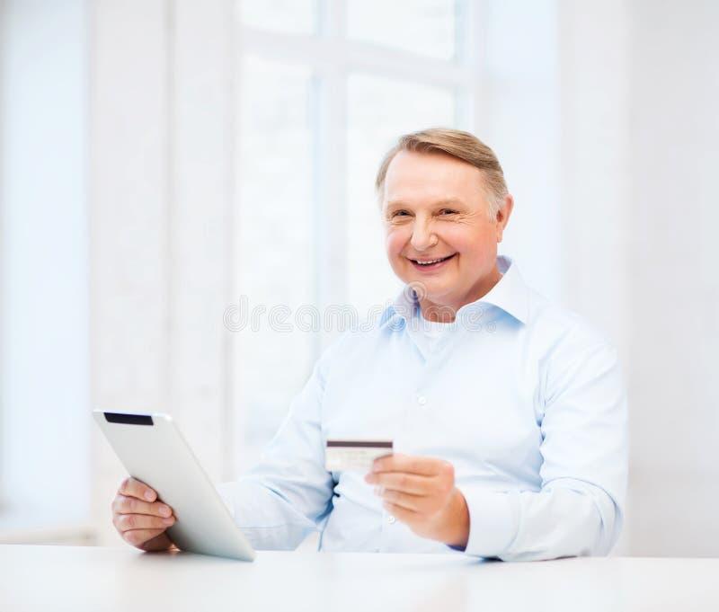 Alter Mann mit Tabletten-PC und -Kreditkarte zu Hause lizenzfreie stockfotos