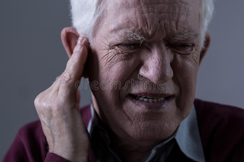 Alter Mann mit Tinnitus stockbild