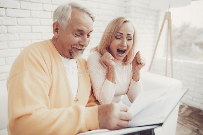 Alter Mann nahe alter Frau mit Dokumenten im Ordner stockfotos