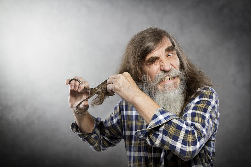 Alter Mann Scissors das Ausschnitt-Haar, das mit verrückter Gesichts-Selbstordnung älter ist lizenzfreies stockfoto