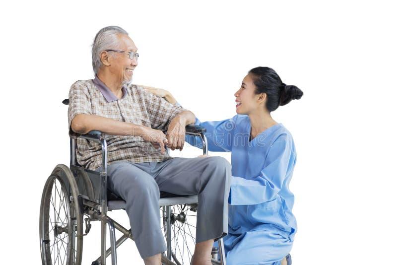 Alter Mann sitzt auf Rollstuhl und Gespräch mit Krankenschwester stockfotos