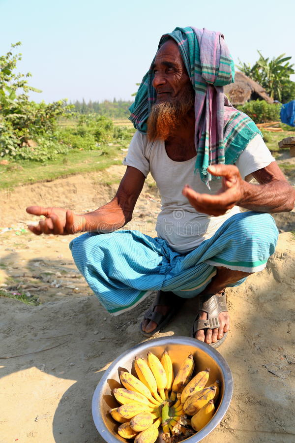 Alter Mann sitzt mit Banane lizenzfreie stockfotografie