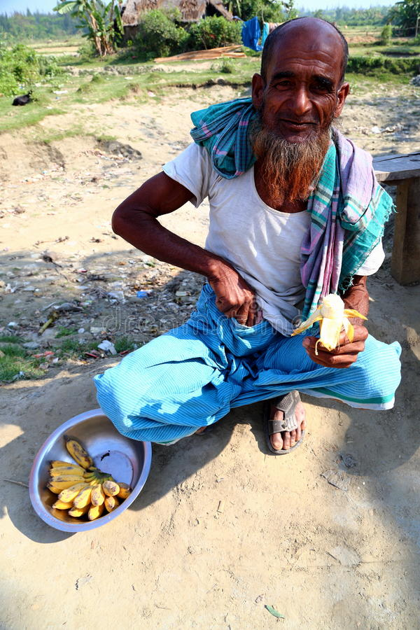 Alter Mann sitzt mit Banane lizenzfreies stockfoto