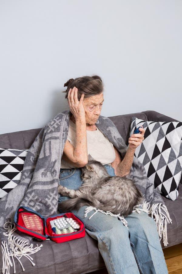 Alter Mann und Diabetes des Themas ältere kaukasische Frau mit dem grauen Haar und den Falten nach Hause auf Sofamaßglukose-Nivea stockfotografie
