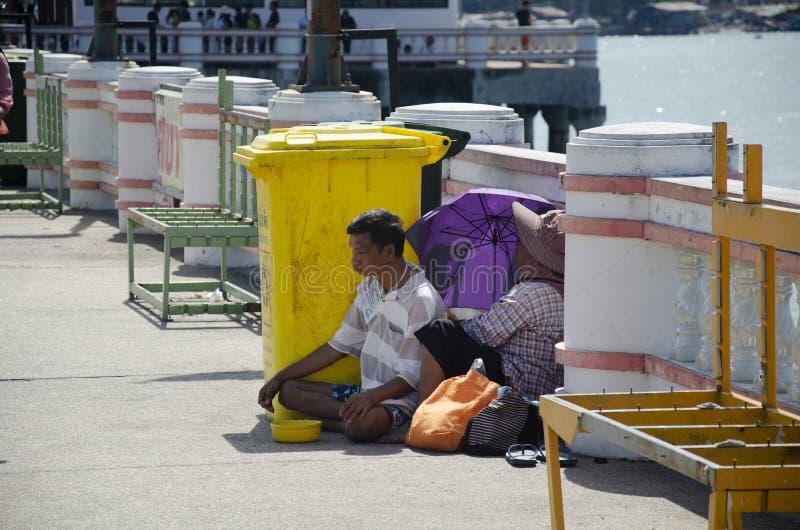 Alter Mann und Frauenbettler, der an der Bahn für das Bitten des Geldes von den Leuten sitzt lizenzfreie stockfotos