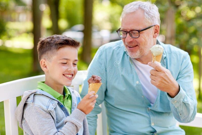 Alter Mann und Junge, die Eiscreme am Sommerpark isst lizenzfreie stockfotos