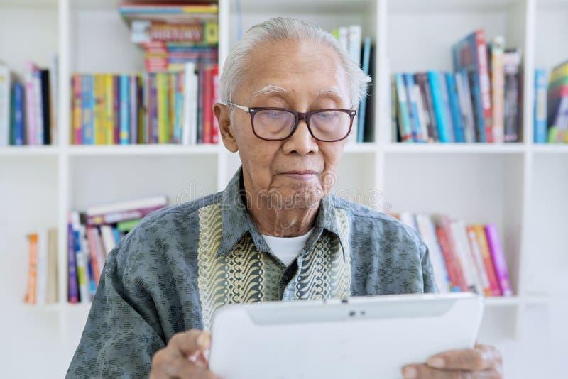 Alter Mann unter Verwendung einer digitalen Tablette in der Bibliothek stockfoto
